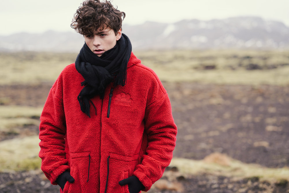 Sundek photoshoot Solon wearing red long jacket at Reykjarnes