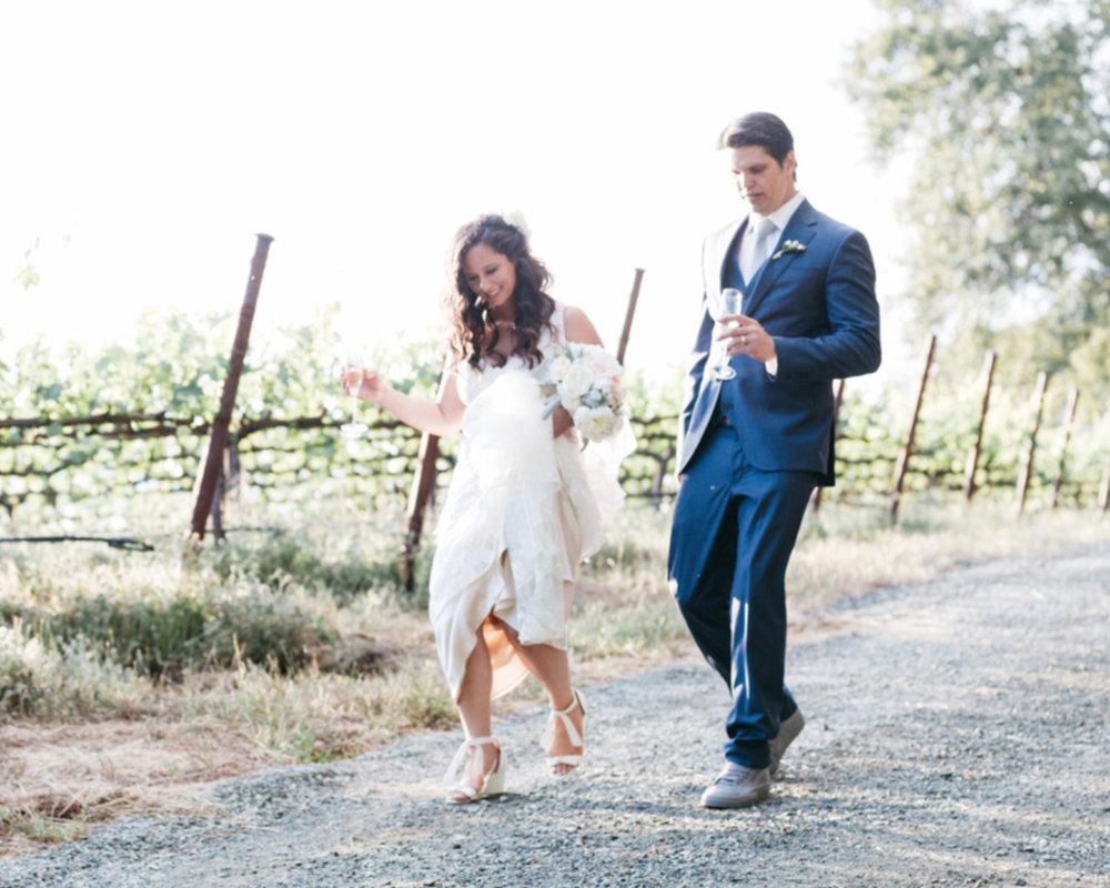bride and groom walking through vineyard with champagne kim baker beauty san jose california makeup artist travel to sutter creek