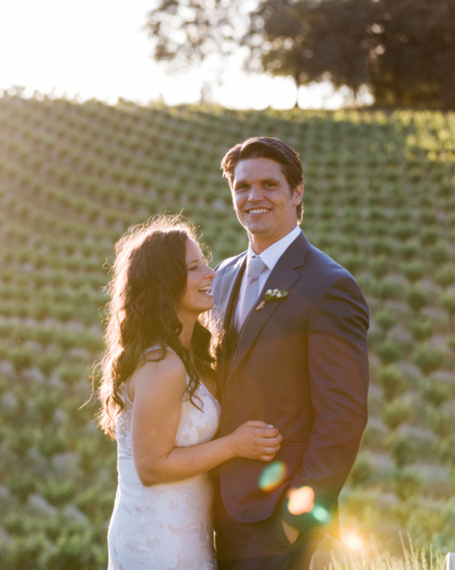 happy smiling married couple bride and groom in vineyard during golden hour with sunflares kim baker beauty san jose california makeup artist travel to sutter creek