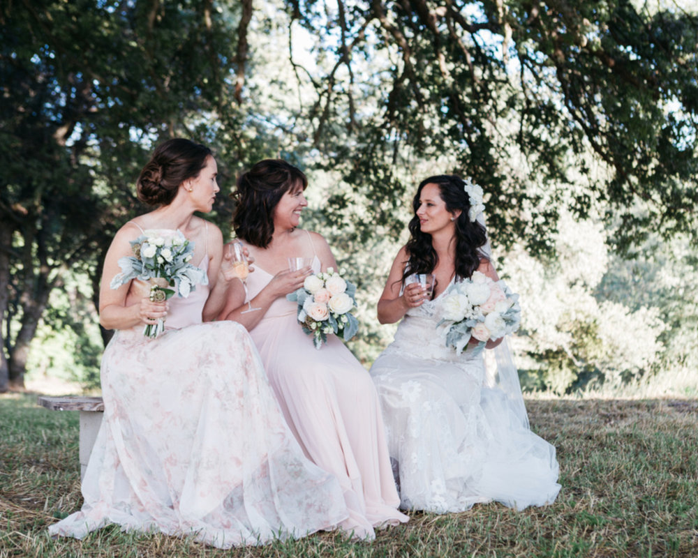bride with new sister in laws on a bench outside under a tree floor length dresses and floral bouquets kim baker beauty san jose california makeup artist travel to sutter creek