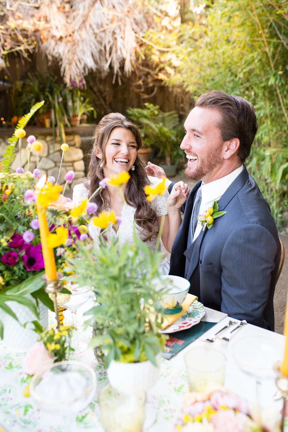 couple laughing together at table with bright flowers and candles kim baker beauty san jose makeup artist at the holly farm in carmel valley