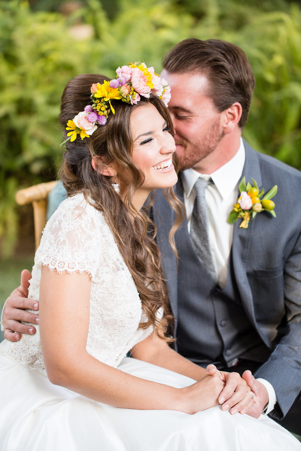 groom kissing bride on cheek bride wearing bright flower crown and short sleeve wedding dress kim baker beauty san jose california makeup artist wedding styled photoshoot at the holly farm in carmel