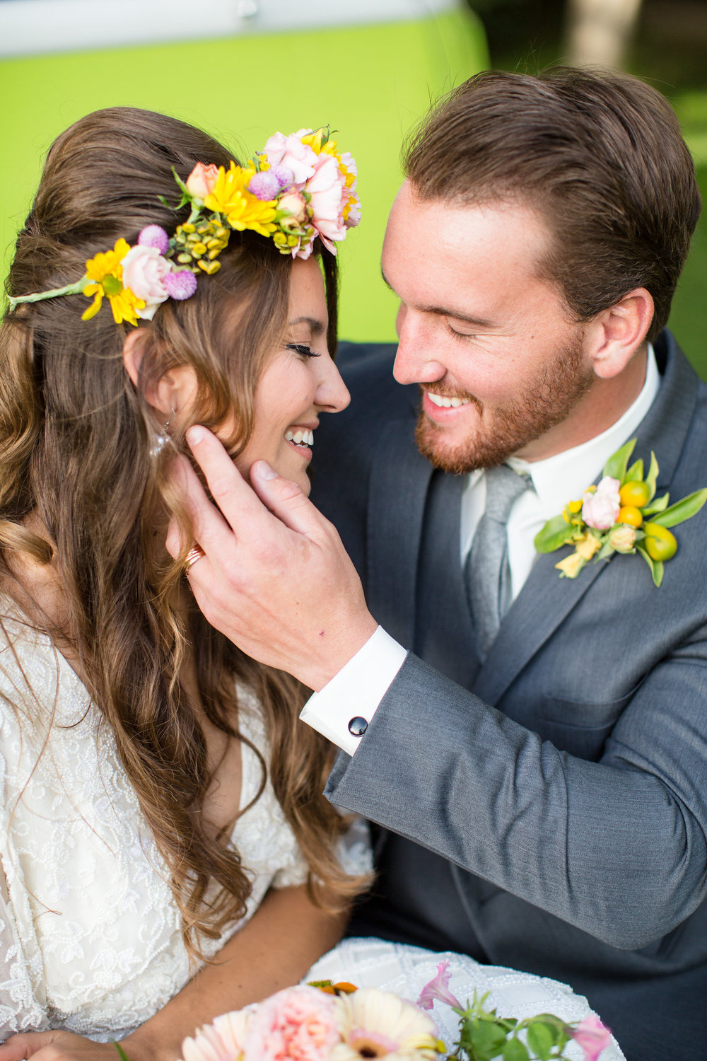 groom holding brides face smiling at one another bride wearing bright flower crown kim baker beauty san jose california makeup artist wedding styled photoshoot at the holly farm in carmel