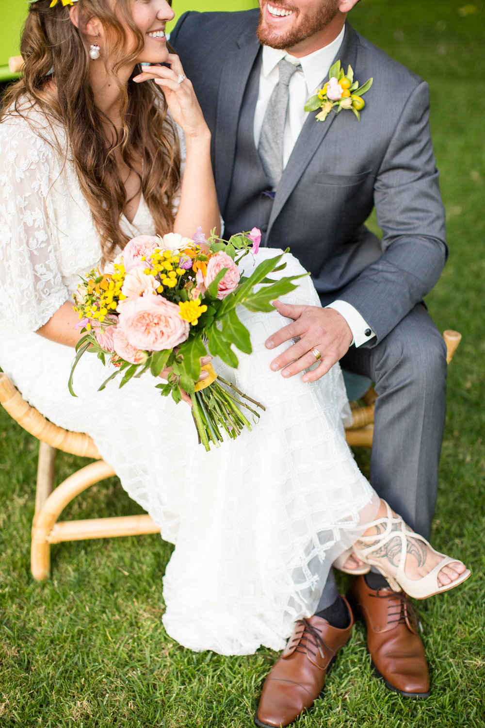 bride and groom sitting together on a chair smiling at each other with tropical bouquet kim baker beauty san jose california makeup artist wedding styled photoshoot at the holly farm in carmel