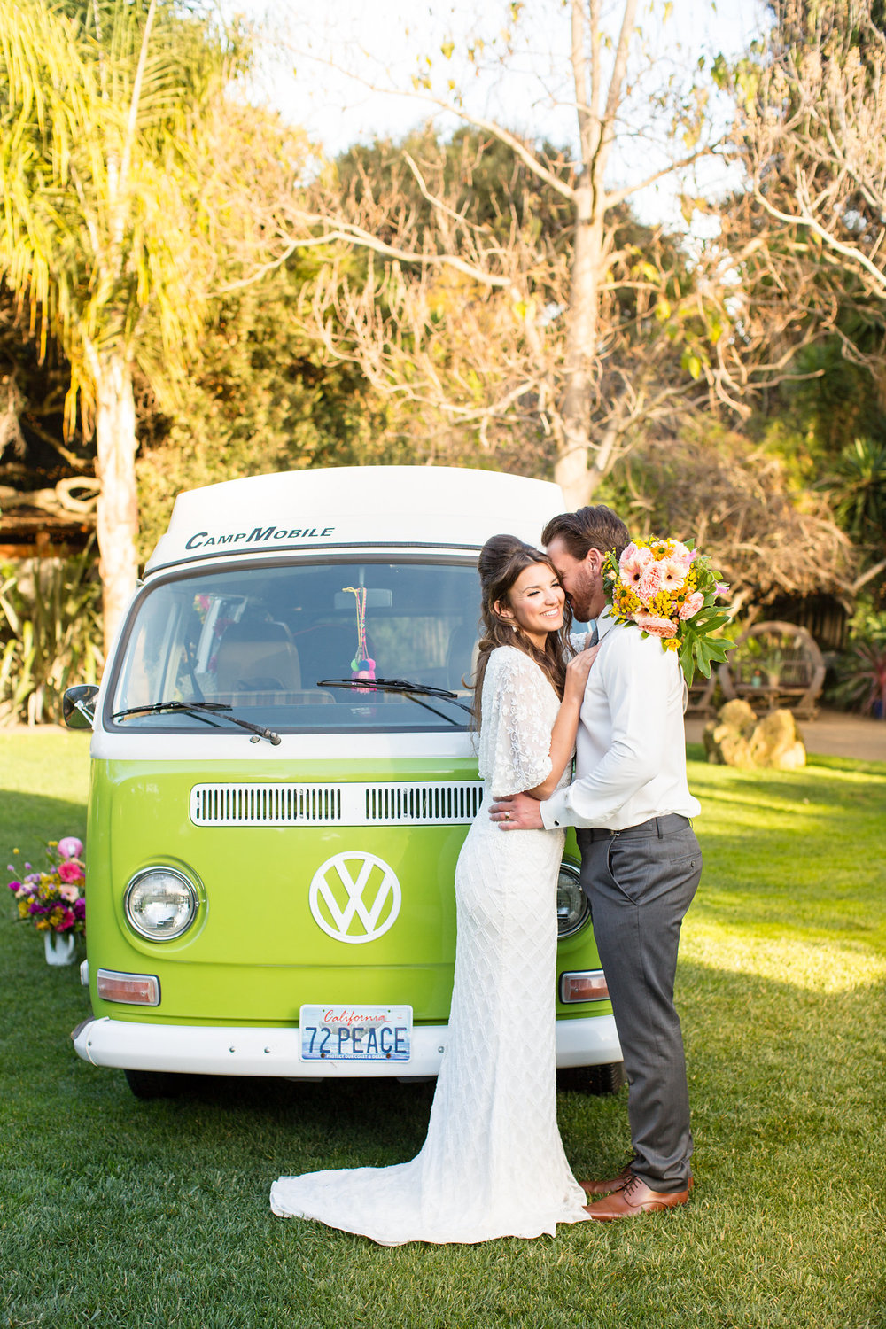 bride in beaded floor length gown with small train hugging groom in front of green vw bus kim baker beauty san jose california makeup artist wedding styled photoshoot at the holly farm in carmel