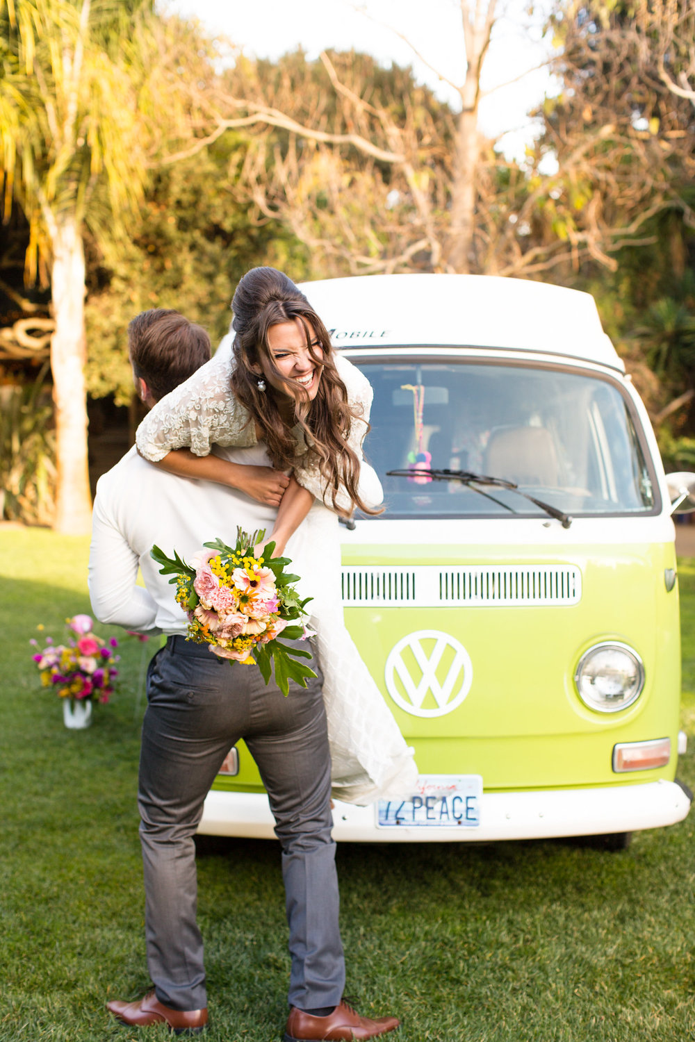 happy and playful couple in front of green vw bus kim baker beauty san jose california makeup artist wedding styled photoshoot at the holly farm in carmel