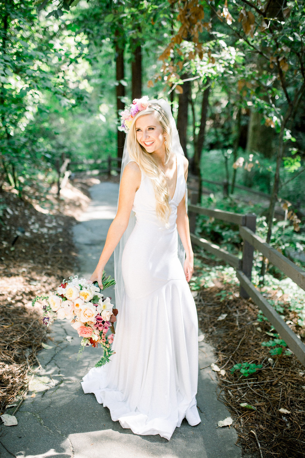 bride in floor length sleeveless deep v neckline wedding gown with veil and flowers in hair kim baker beauty san jose california makeup artist