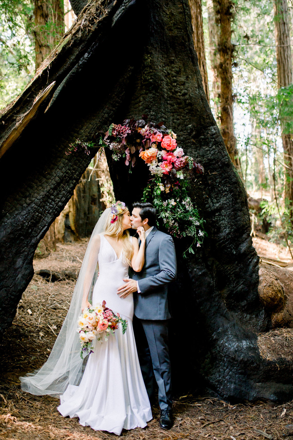 bride and groom in the redwoods with flowers in the trees and bouquet kim baker beauty san jose california makeup artist