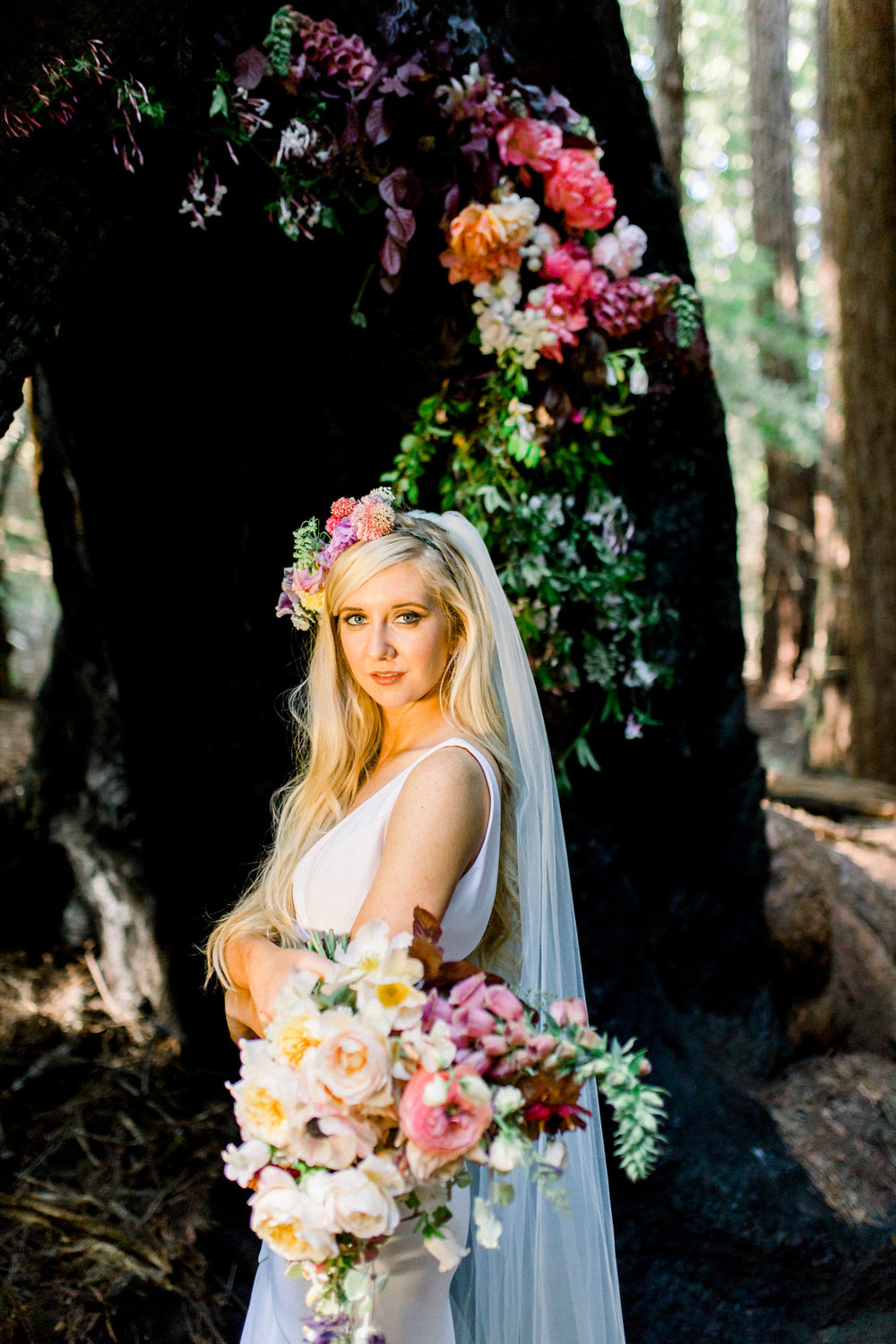 bride in redwoods wearing floor length sleeveless deep v neckline wedding gown with veil and flowers in hair kim baker beauty san jose california makeup artist