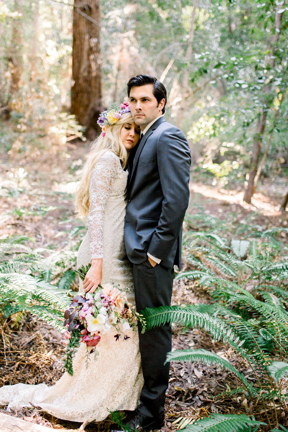 groom holding bride wearing lace long sleeve floor length wedding dress holding bouquet in redwoods kim baker beauty san jose claifornia makeup artist