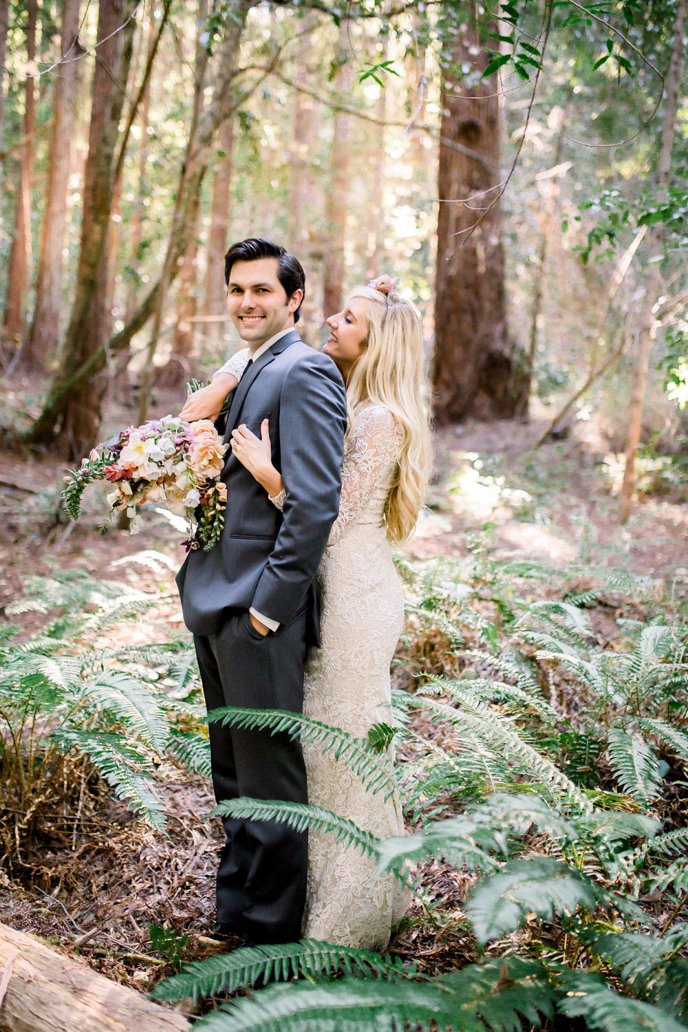 bride wearing lace long sleeve floor length wedding dress holding bouquet and hugging groom in redwoods kim baker beauty san jose claifornia makeup artist