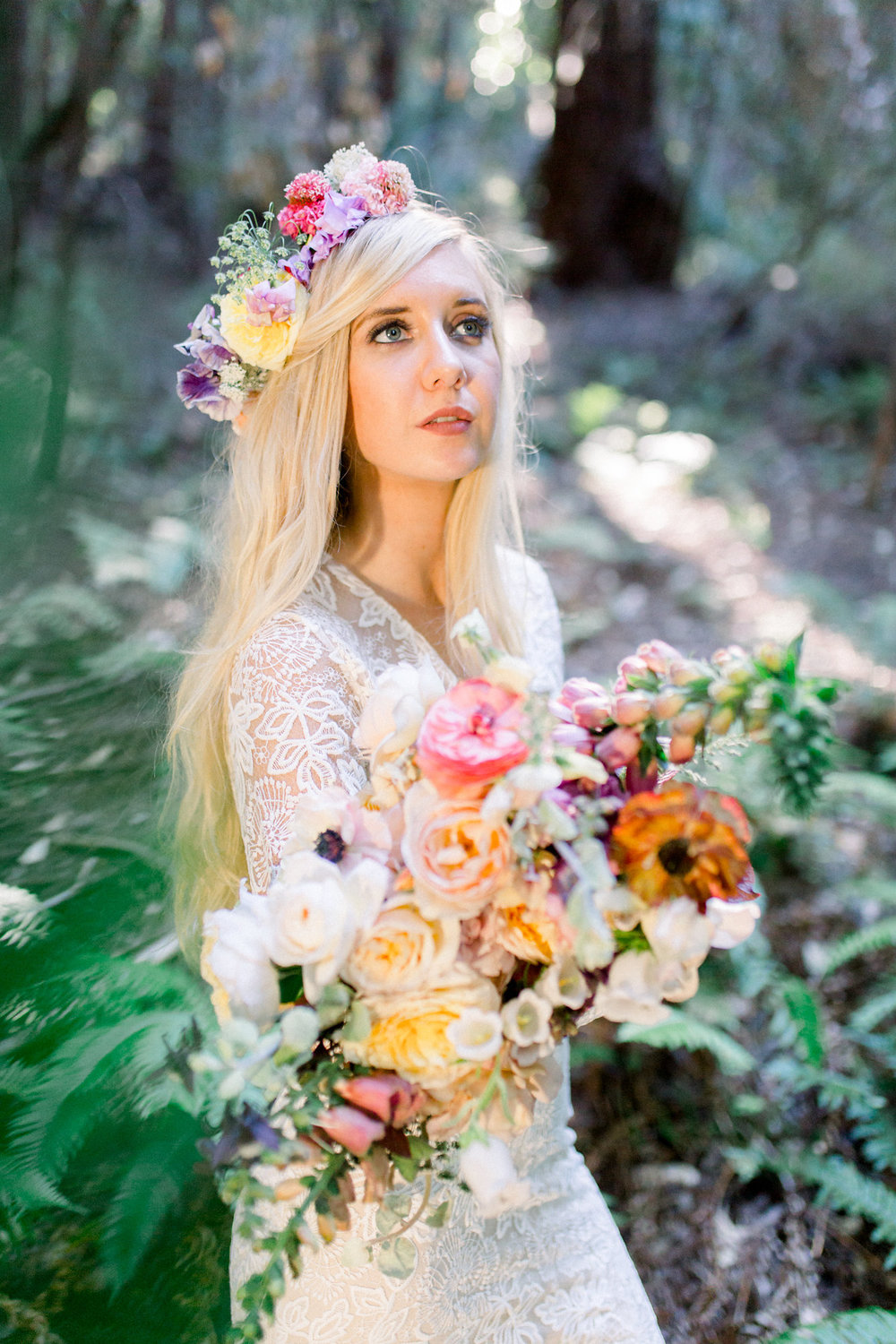 bride wearing lace long sleeve wedding dress flower crown and holding floral bouquet in redwoods kim baker beauty san jose california makeup artist