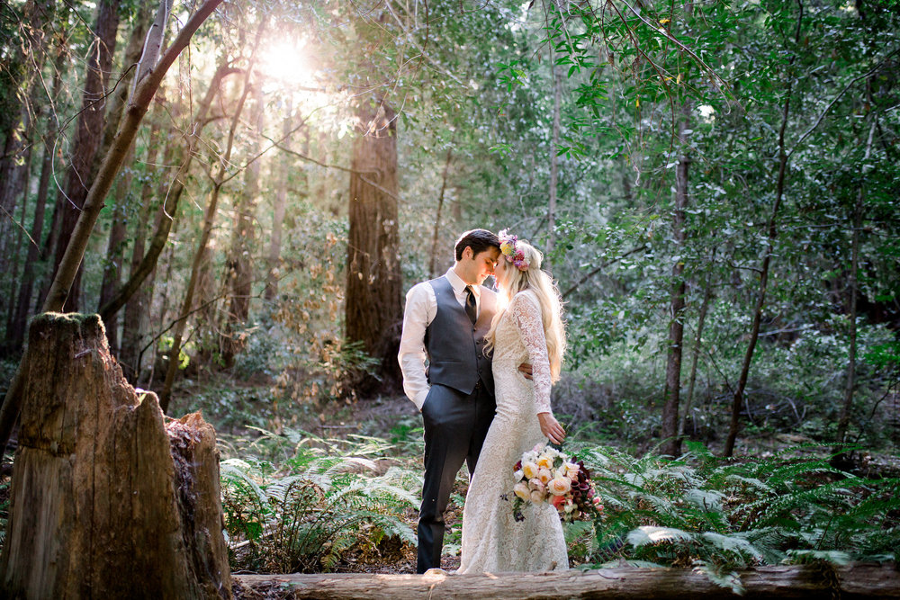 bride wearing lace long sleeve floor length wedding dress with small train flower crown and holding floral bouquet in redwoods kim baker beauty san jose california makeup artist
