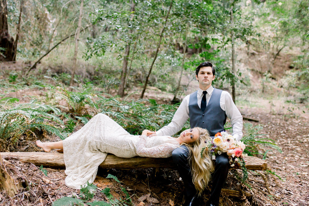 bride laying on redwood tree with groom wearing lace long sleeve floor length wedding dress with small train flower crown kim baker beauty san jose california makeup artist