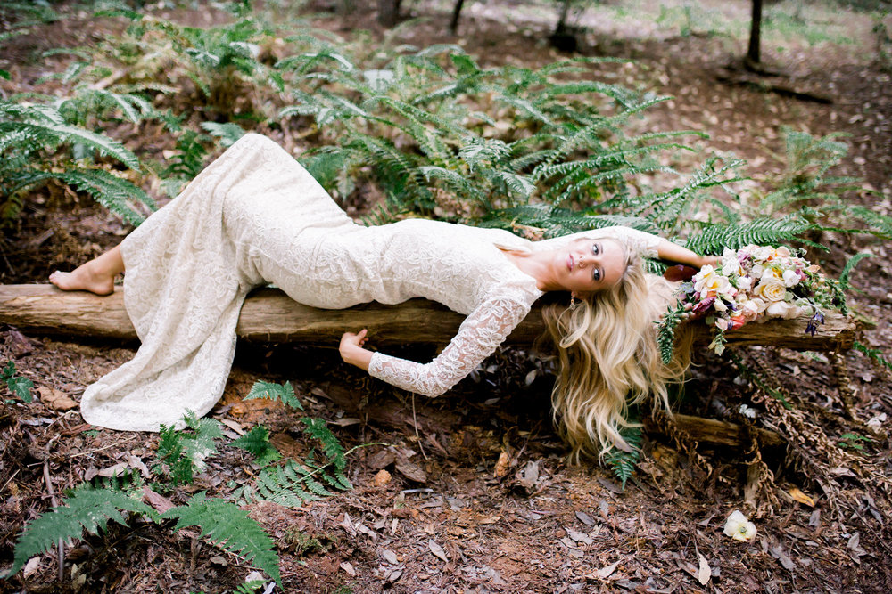 bride laying on redwood tree wearing lace long sleeve floor length wedding dress with small train flower crown kim baker beauty san jose california makeup artist