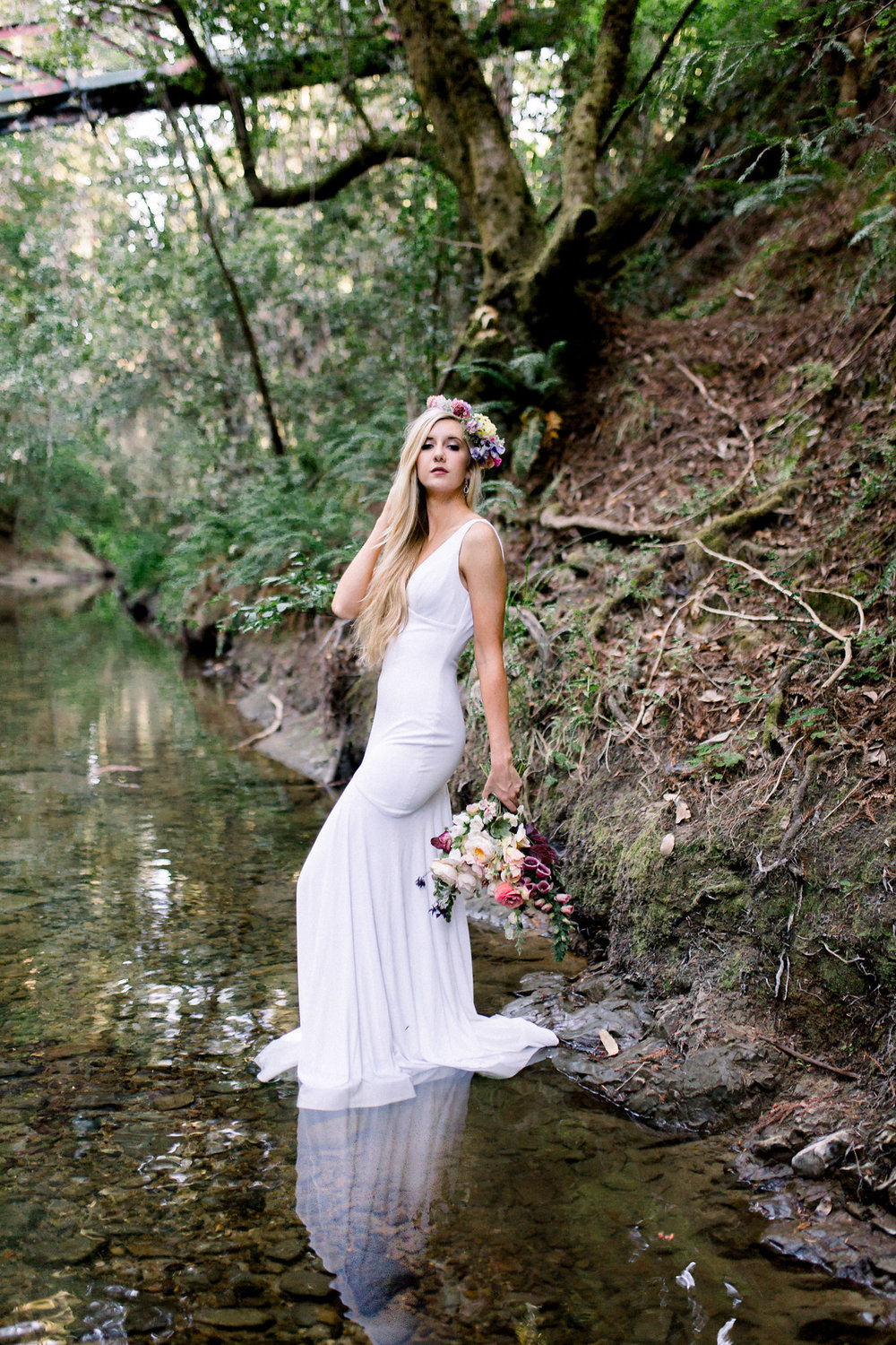 bride standing in creek wearing flower crown in floor length sleeveless white wedding gown kim baker beauty san jose california makeup artist