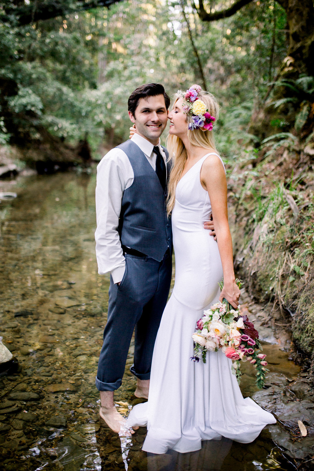 groom standing in creek with bride wearing sleeveless deep v floor length white wedding gown with flower crown holding bouquet kim baker beauty san jose california makeup artist
