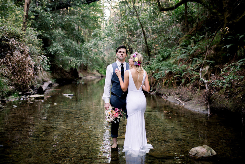 groom standing in creek with bride wearing sleeveless backless floor length white wedding gown with flower crown holding bouquet kim baker beauty san jose california makeup artist