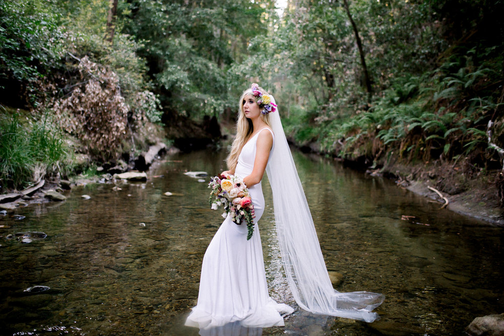 bride standing in creek wearing long veil flower crown in floor length sleeveless white wedding gown kim baker beauty san jose california makeup artist