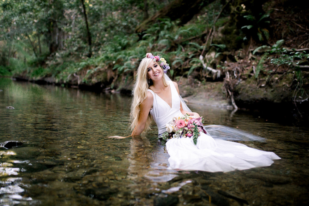 bride sitting in creek wearing long veil flower crown in floor length sleeveless white wedding gown kim baker beauty san jose california makeup artist