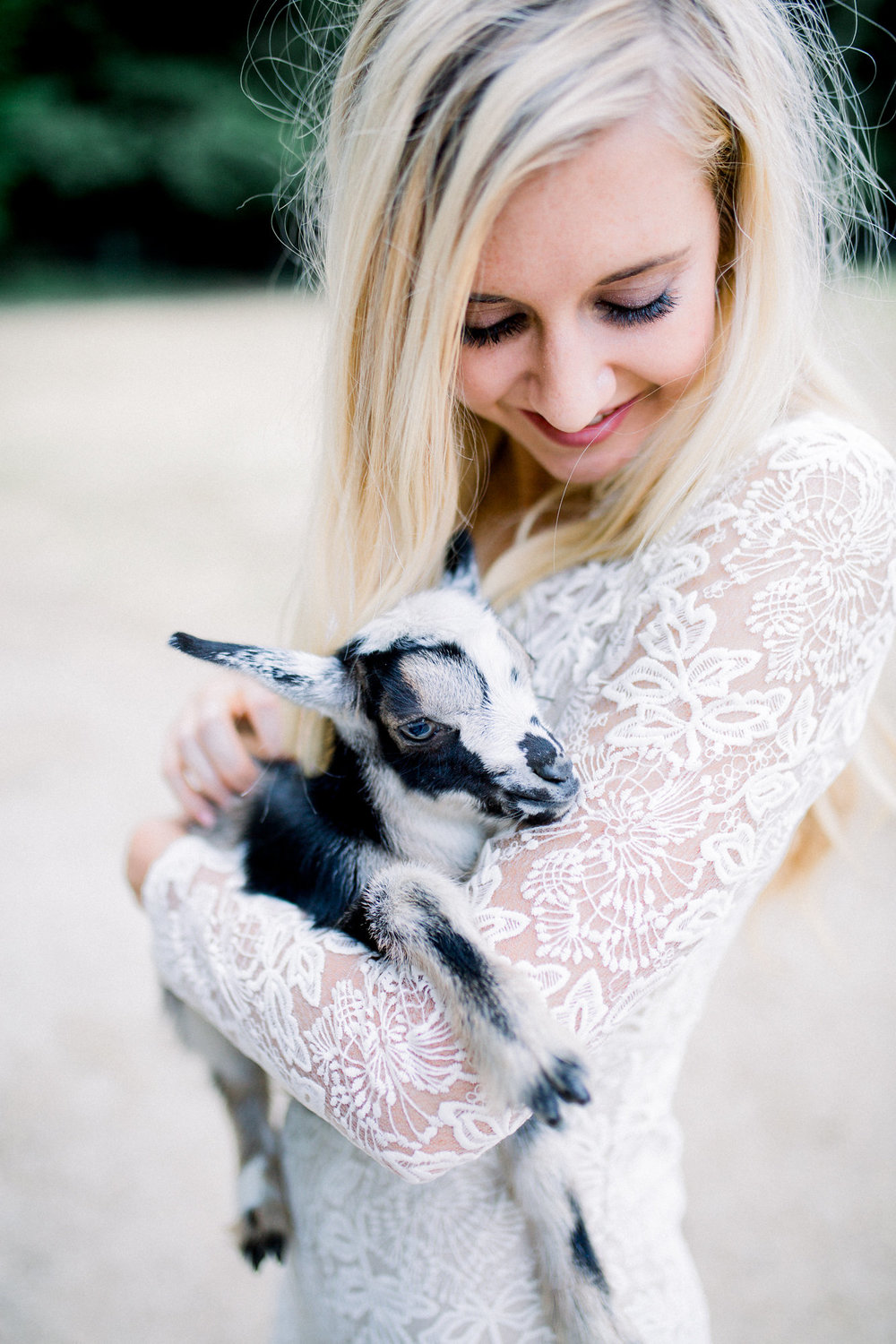 bride in long sleeve lace bridal dress holding baby goat kim baker beauty san jose caifornia makeup artist