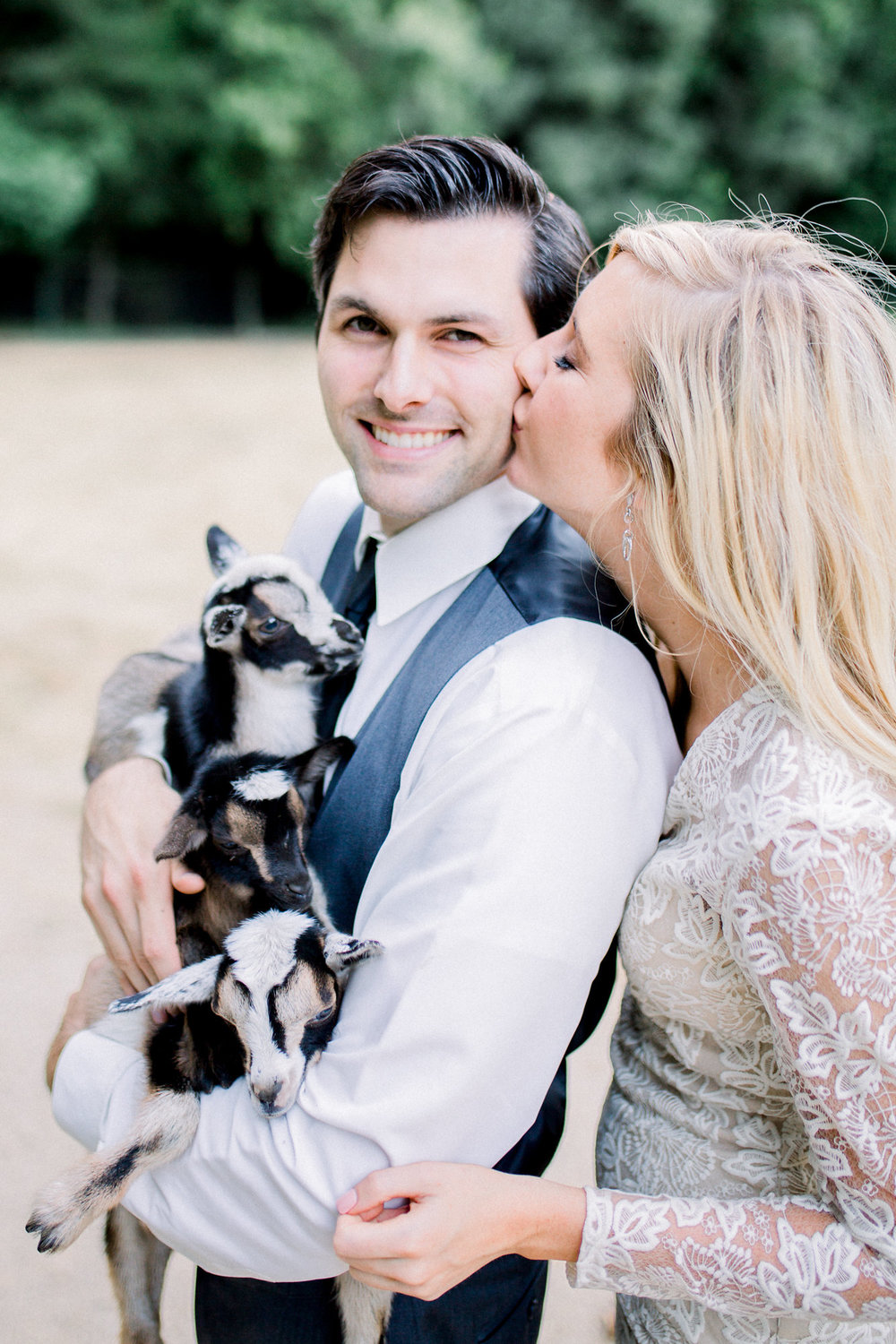 bride in long sleeve lace wedding dress holding baby goats with groom kim baker beauty san jose california makeup artist