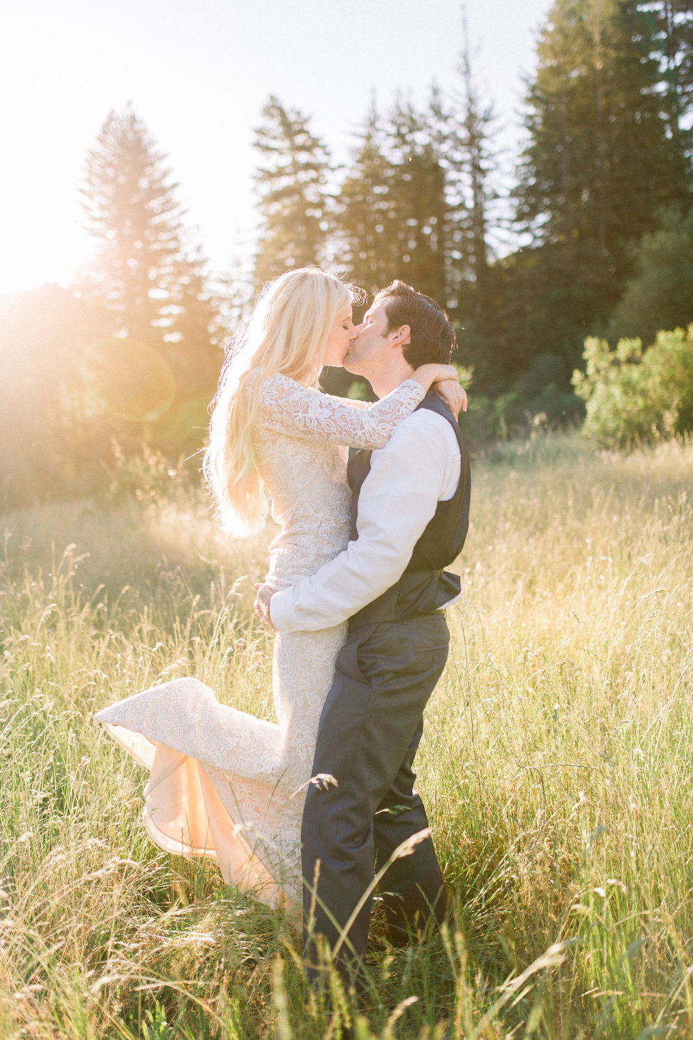 groom being playful with bride in lace long sleeve white wedding gown in grassy field during golden hour kim baker beauty san jose california makeup artist
