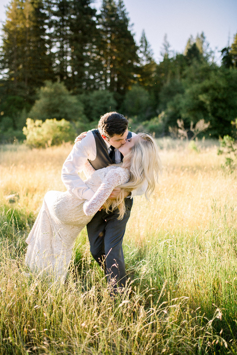 groom kissing bride in lace long sleeve white wedding gown in grassy field during golden hour kim baker beauty san jose california makeup artist