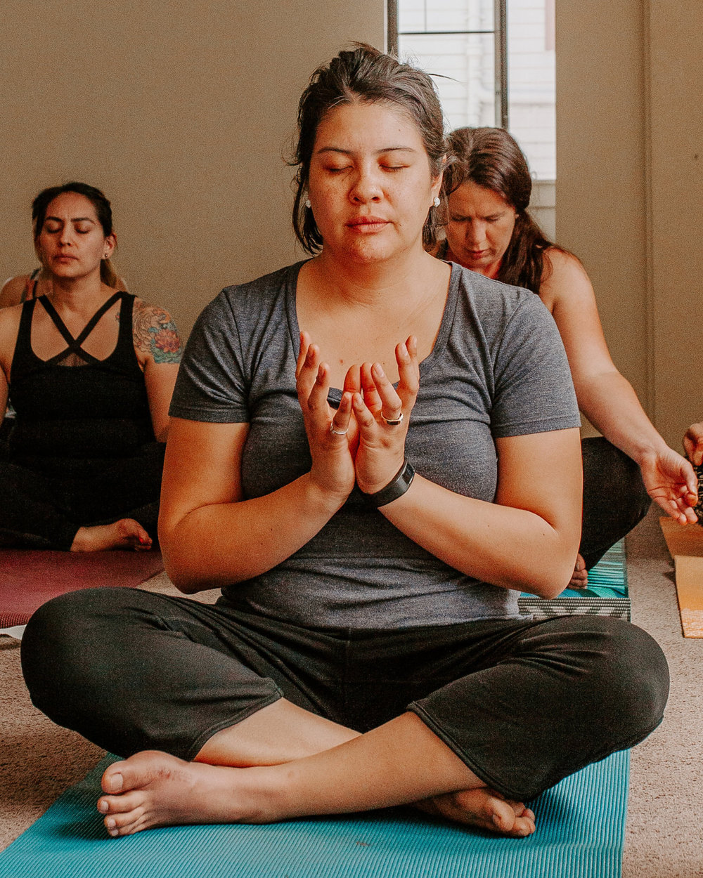 women meditating in lotus pose of yoga during self0care event by kim baker beauty san jose california makeup artist photo by catie belle photography