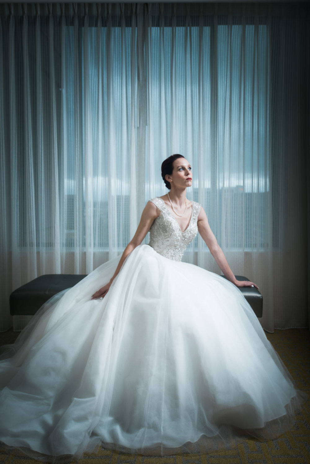 bride in gown with large tulle bottom and beaded cap sleeve top in hotel room makeup is classic with red lip by kim baker beauty san jose california makeup artist