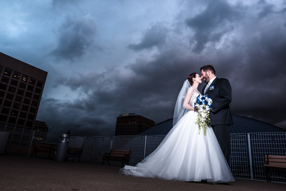 bride and groom on rooftop with moody sky and a lot of clowds large floral bouquet makeup by kim baker beauty san jose california makeup artist