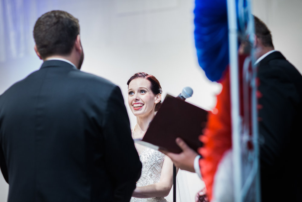 bride smiling at groom getting married at the altar at the tech museum makeup by kim baker beauty san jose california makeup artist