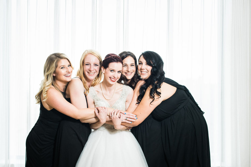 bride with bridesmaids wearing black dresses in bridal suite makeup by kim baker beauty san jose california makeup artist