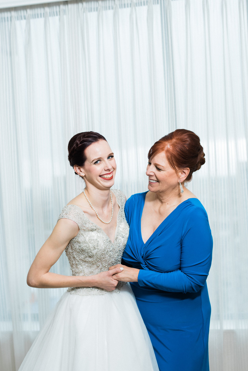 bride with mother in blue dress and up dos in bridal suite makeup is clean and classic with warm tones for mom and a red lip for the bride by kim baker beauty san jose california makeup artist