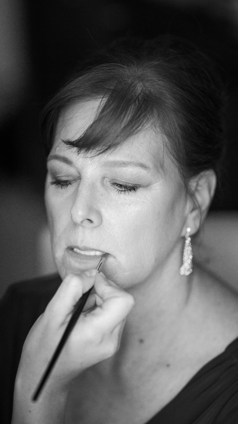 black and white photo of mother of bride having makeup applied with hair in an updo by kim baker beauty san jose california makeup artist