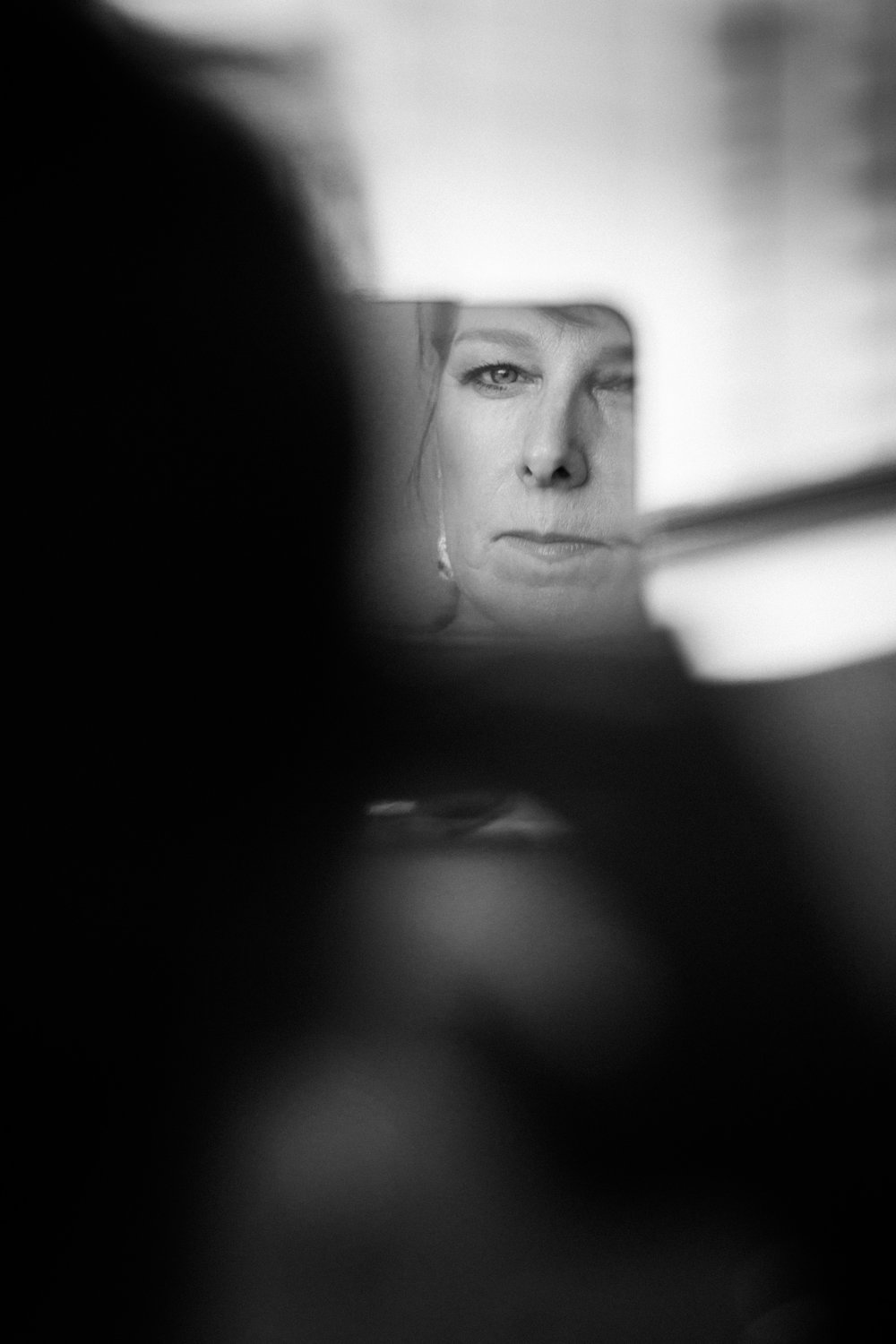 mother of bride looking in a tom form mirror after makeup completed by kim baker beauty san jose california makeup artist black and white photo