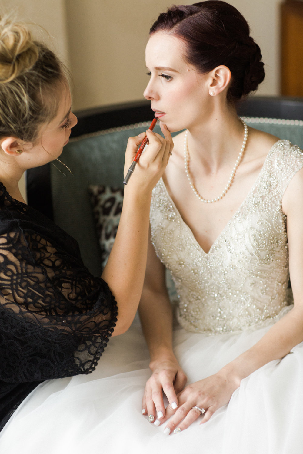 kim baker beauty san jose california makeup artist apply urban decause red lip liner to bride for her classic bridal look beaded cap sleeve wedding gown