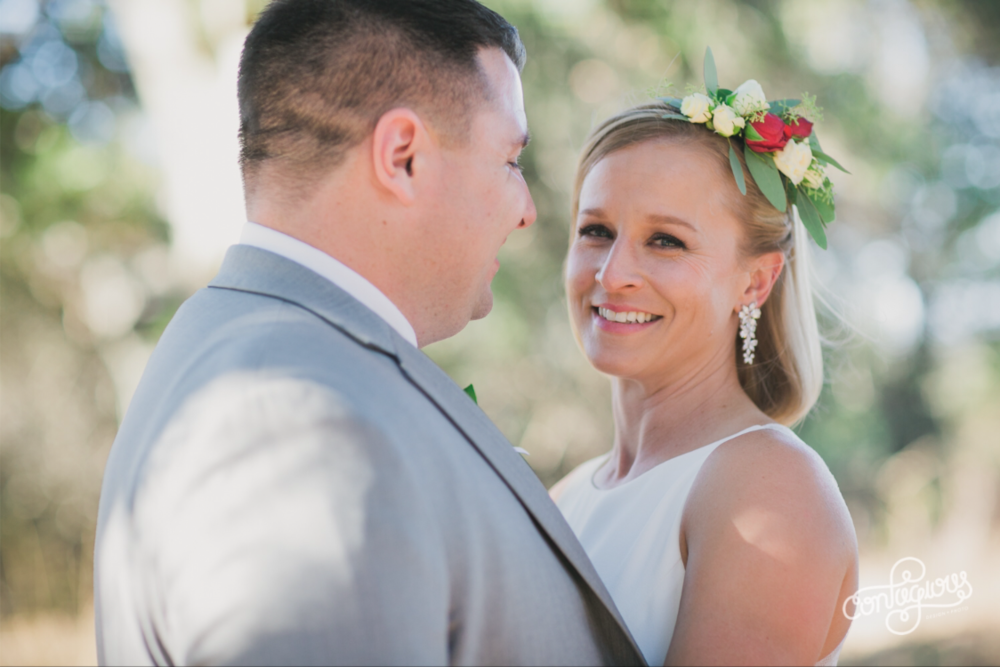 bride smiling at the camera wearing flower crown with groom glowing at bride natural subtle glam bridal makeup applied by kim baker beauty san jose california makeup artist at picchetti winery