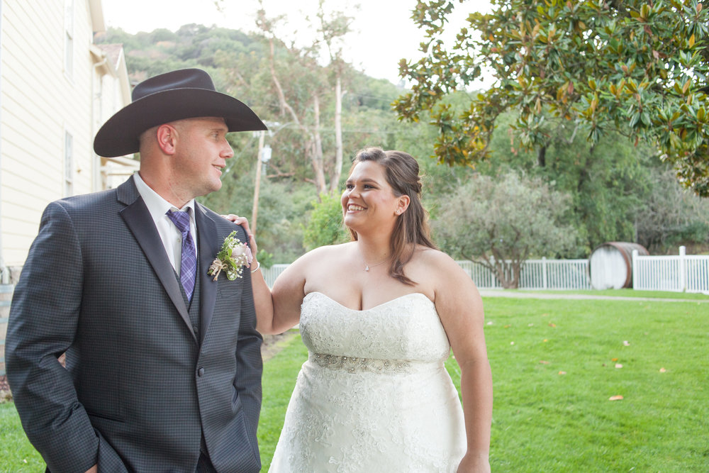 bride reaching for groom wearing cowboy hat for first look at picchetti winery wedding makeup by kim baker beauty san jose california makeup artist