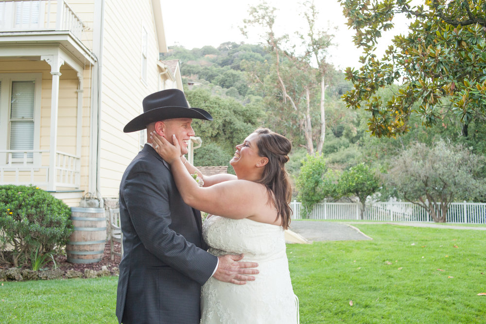 bride squeezing groom's face lovingly at picchetti winery wedding in cupertino makeup by kim baker beauty san jose california makeup artist