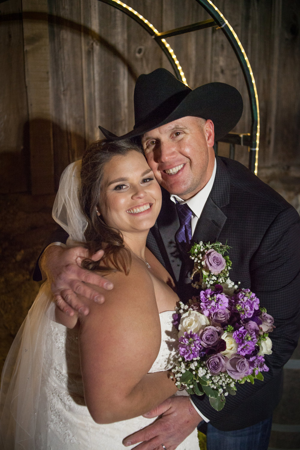 bride with purple flower bouquet and wearing veil with groom in cowboy hat at night ceremony at picchetti winery makeup by kim baker beauty san jose california makeup artist