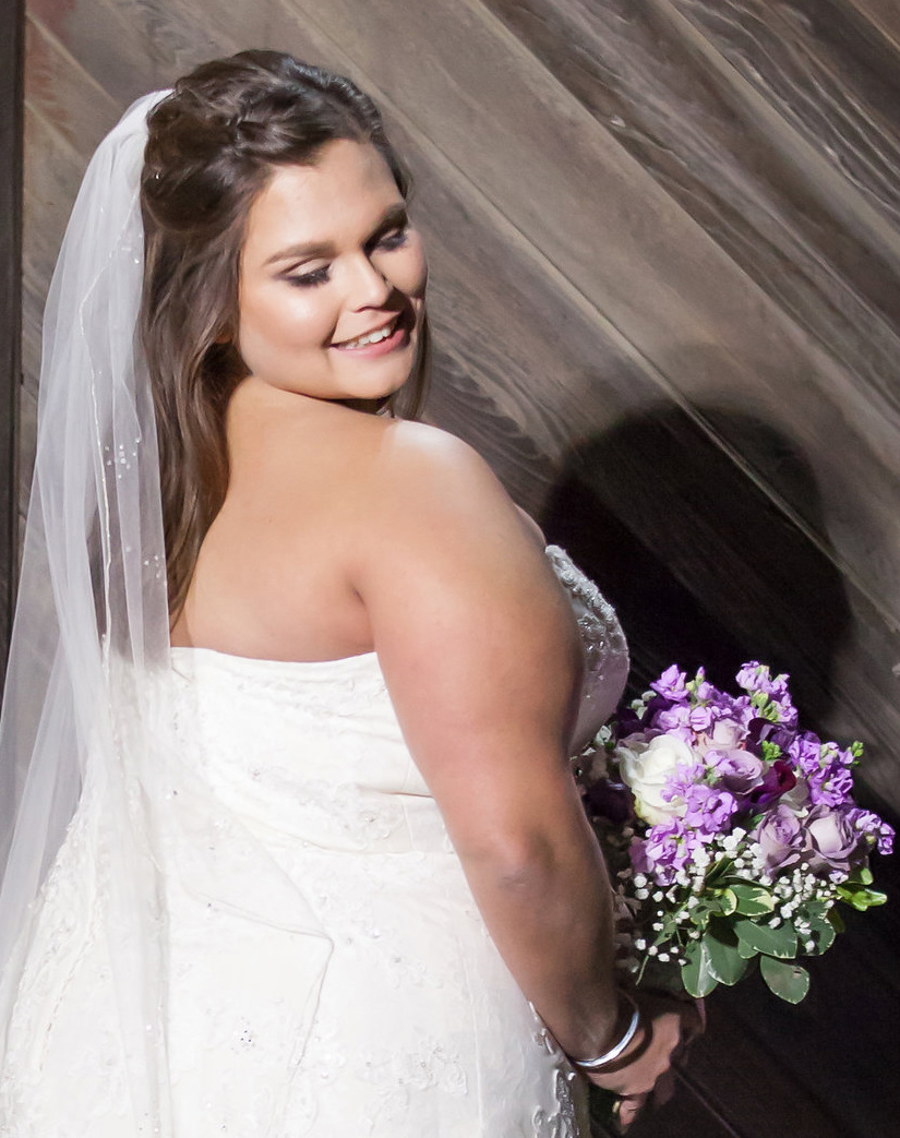 glowing bride wearing veil and purple floral bouquet looking over shoulder bridal subtle natural glam makeup by kim baker beauty san jose california makeup artist at picchetti winery in cuptertino