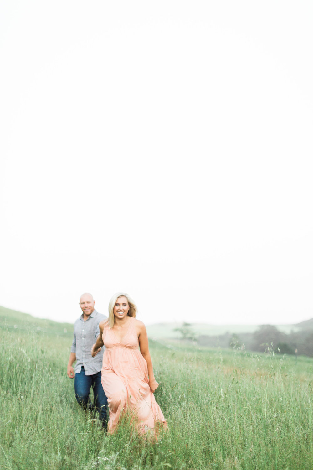 engagement session in grassy fields of sonoma couple playful and in love soft subtle natural makeup by kim baker beauty san jose california makeup artist