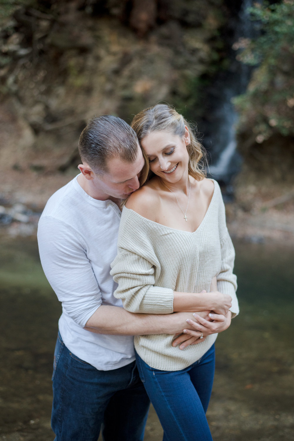 outdoor engagement photoshoot in santa cruz next to creek bride wearing off the shoulder sweater jeans and booties soft glam neutral makeup by kim baker beauty san jose california makeup artist