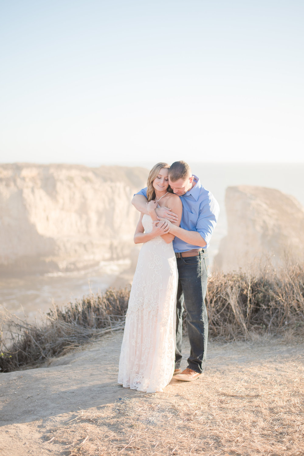 outdoor engagement photoshoot in santa cruz on cliff near ocean at golden hour bride wearing cream lace maxi dress soft glam neutral makeup by kim baker beauty san jose california makeup artist