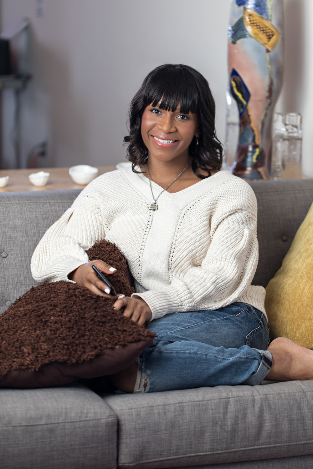 sharon hadden sitting on cozy couch in cream sweater and ripped jeans with glowing makeup by kim baker beauty san jose california makeup artist