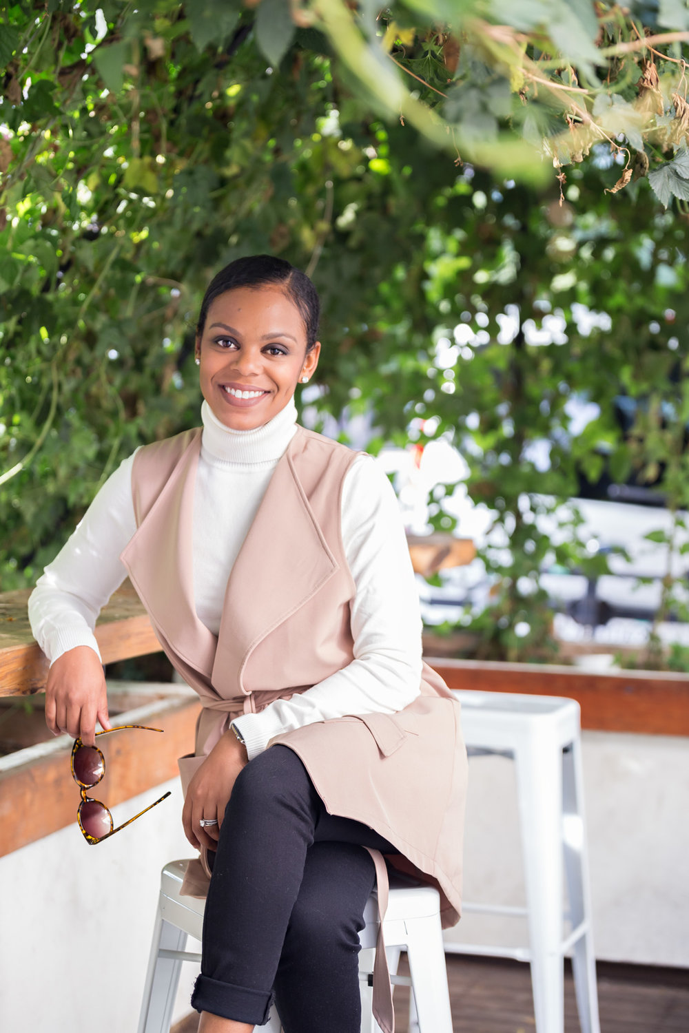erica estrada of e33 bay area wedding coordinating sitting outside in white turtle neck and brown vest with soft neutral makeup by kim baker beauty san jose california makeup artist