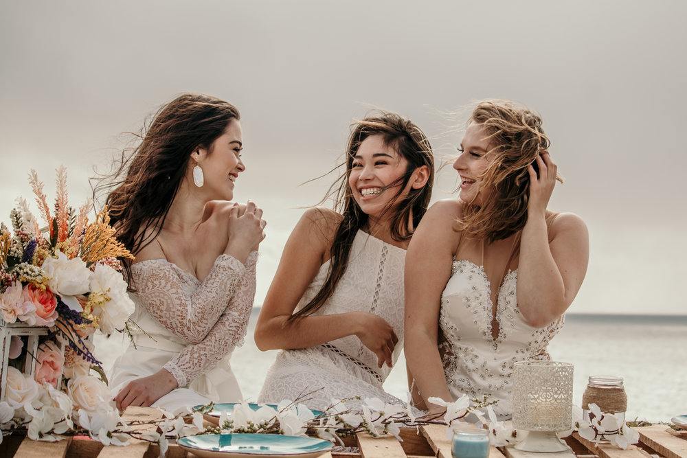 three models sitting laughing together in white lacey dresses at panther beach in santa cruz simple clean makeup by kim baker beauty san jose california makeup artist