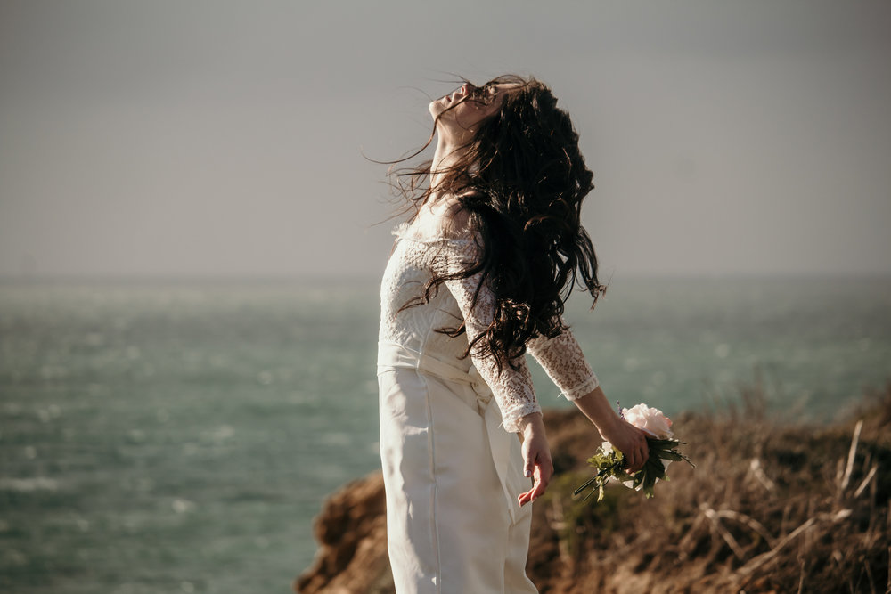 artistic image of model at panther beach in santa cruz where white bridal lacey jumpsuit holding rose messy hair makeup by kim baker beauty san jose california makeup artist
