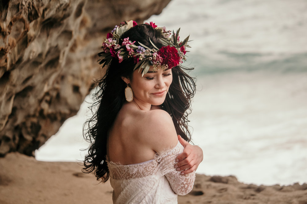 happy bridal model in lacey off the shoulder dress with colorful flower crown at panther beach in santa cruz wearing soft romantic natural makeup by kim baker beauty san jose california makeup artist